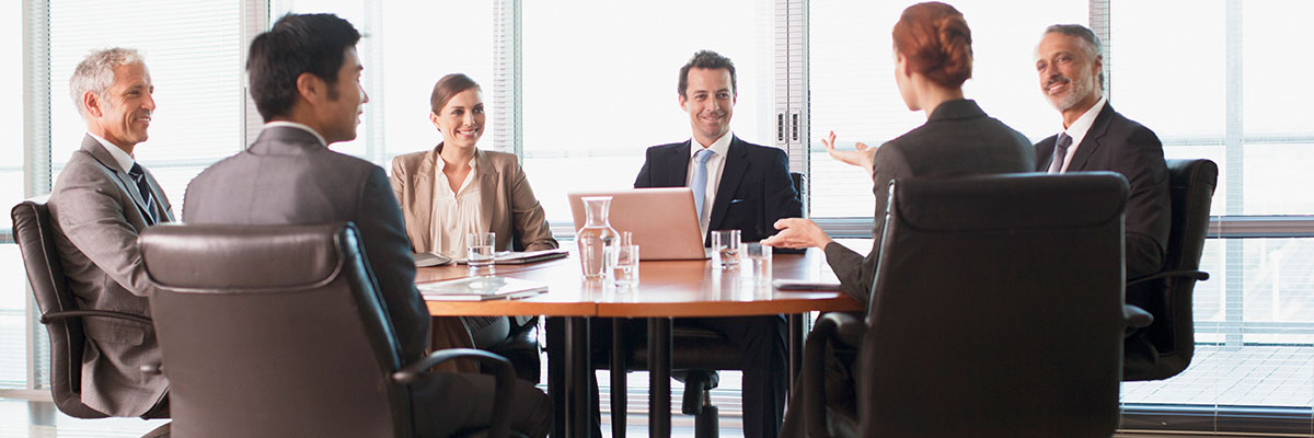 Business people sitting around a board room table